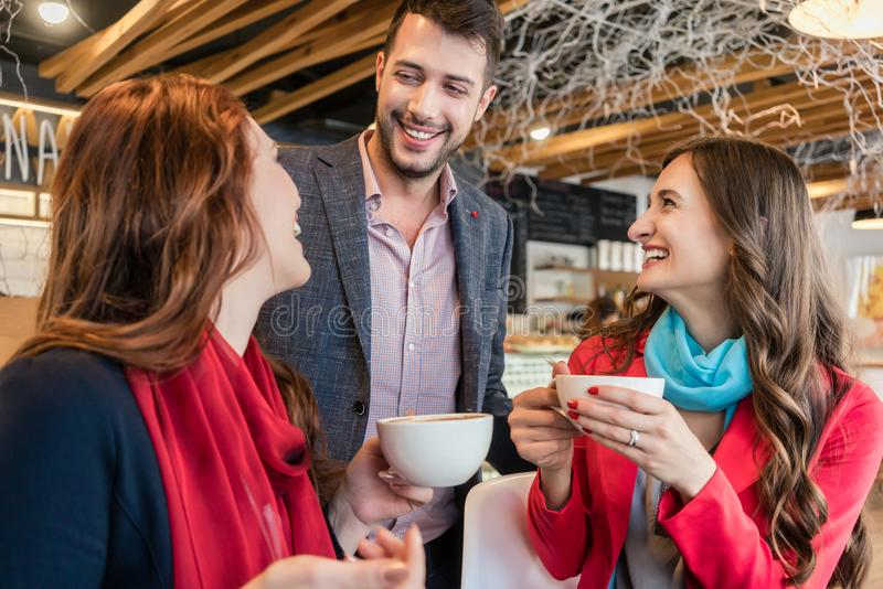 Attractive young woman meeting an old friend while enjoying a hot drink stock photography