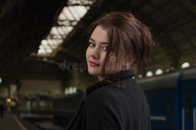 Attractive young woman millenial in black clothes and a hat and glasses at the railway station next to the train royalty free stock photos