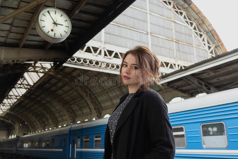 Attractive young woman millenial in black clothes and a hat and glasses at the railway station next to the train royalty free stock image