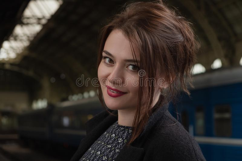 Attractive young woman millenial in black clothes and a hat and glasses at the railway station next to the train royalty free stock photo