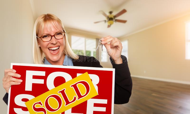 Attractive Young Woman with New Keys and Sold Real Estate Sign In Empty Room of House royalty free stock images