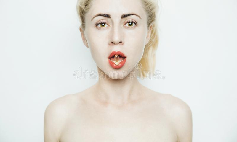 Attractive Young Woman Opened Mouth Holding Pill in White Teeth Mouth, Front View Portrait Hälsosam princip om att man ska äta nä royaltyfria foton