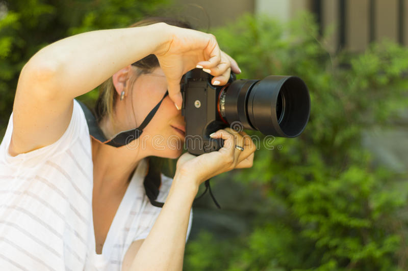 Attractive young woman photographer taking photos with dslr camera outdoors. Copy space stock images