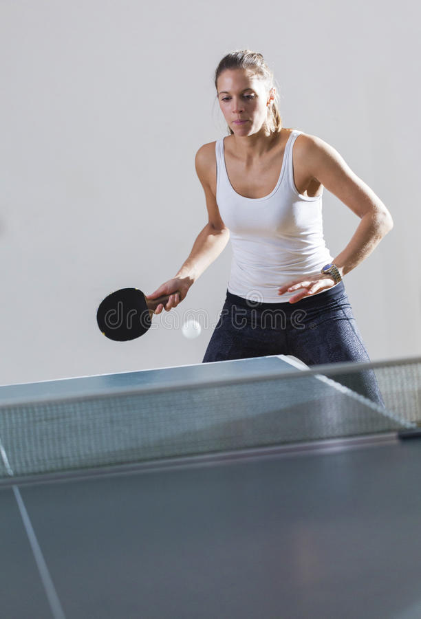 Attractive young woman playing table tennis indoors stock photography