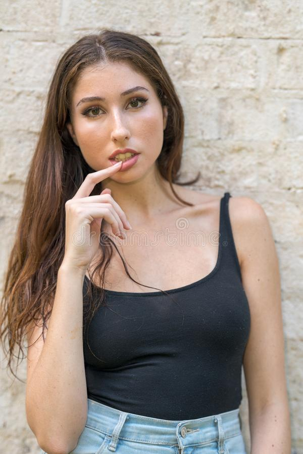 Attractive young woman posing in a tank top finger rubbing lips flirty stock image