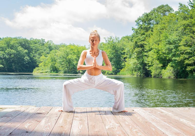 Attractive woman is practicing yoga, doing Stupasana exercise, standing in Goddess pose near lake stock photo