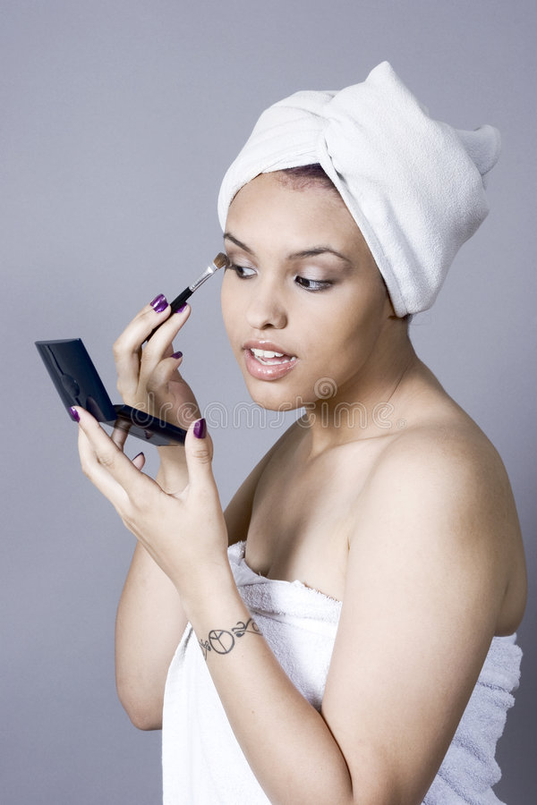 Attractive young woman putting on makeup stock photos