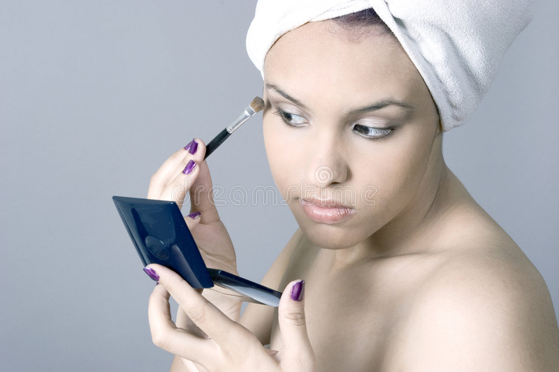 Attractive young woman putting on makeup royalty free stock image