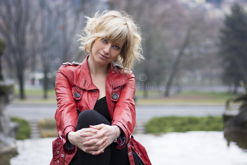 Attractive young woman with red leather jacket. Sitting in a park royalty free stock images