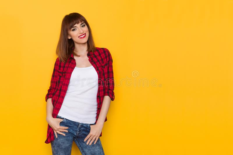 Attractive Young Woman In Red Lumberjack Shirt. Smiling young woman in unbuttoned red lumberjack shirt and jeans is smiling and looking at camera. Three quarter stock photography