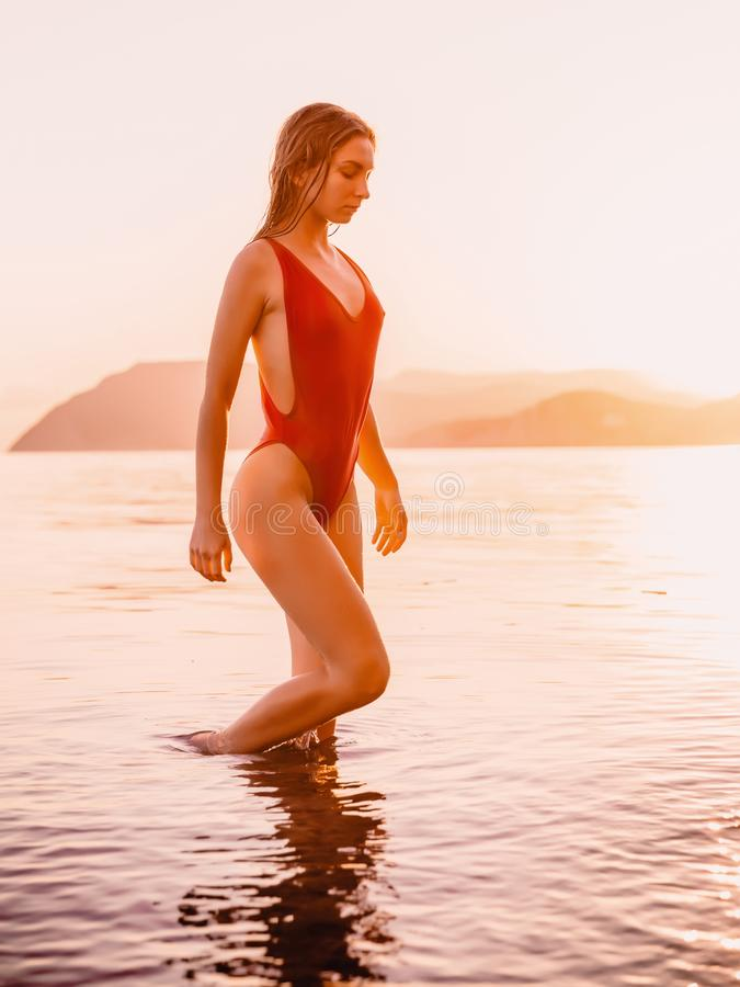 Attractive young woman in red swimwear bikini relaxing on beach with warm sunset colors royalty free stock photos