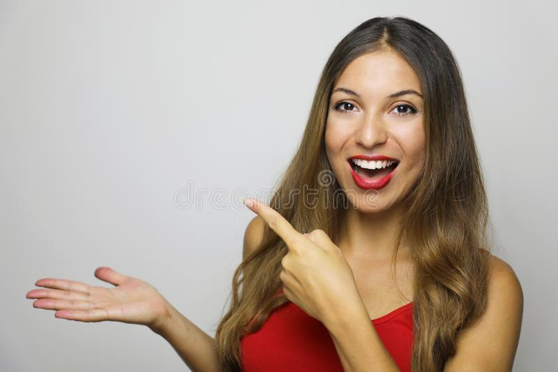 Attractive young woman with red tank top showing on her hand and pointing finger your product / logo on gray background. Copy space stock photography