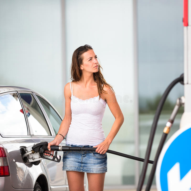 Attractive, young woman refueling her car in a gas station royalty free stock photo