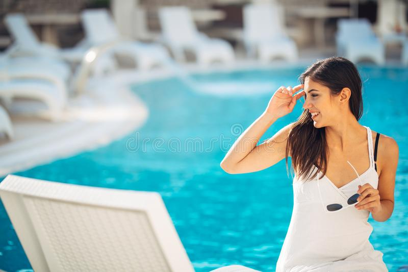 Attractive young woman relaxing at nluxury vacation resort pool.Enjoying summer.Vacation mood.Girl at travel spa resort pool.Flirt. Ing female.Traveling alone stock image