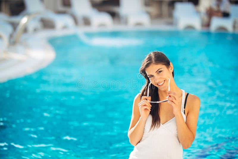 Attractive young woman relaxing at nluxury vacation resort pool.Enjoying summer.Vacation mood.Girl at travel spa resort pool.Flirt. Ing female.Traveling alone royalty free stock photo