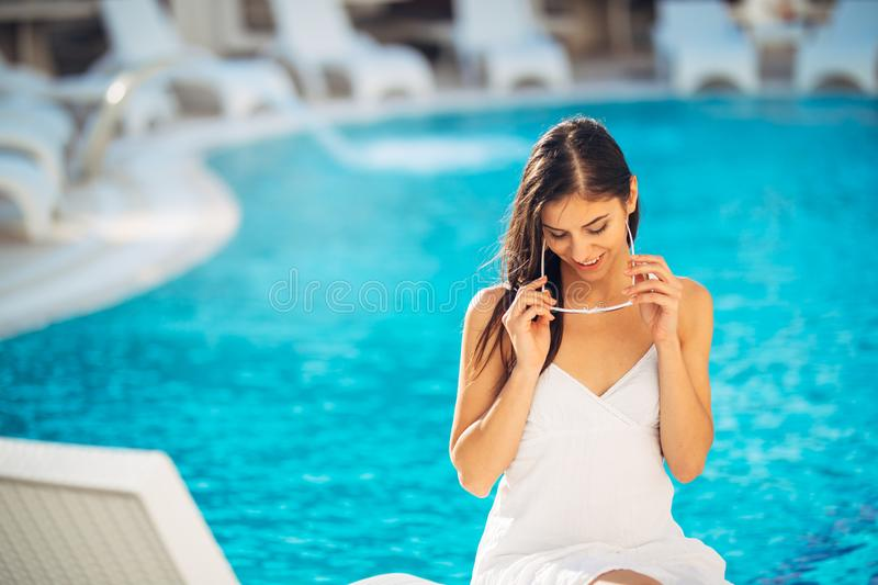 Attractive young woman relaxing at nluxury vacation resort pool.Enjoying summer.Vacation mood.Girl at travel spa resort pool.Flirt. Ing female.Traveling alone royalty free stock images
