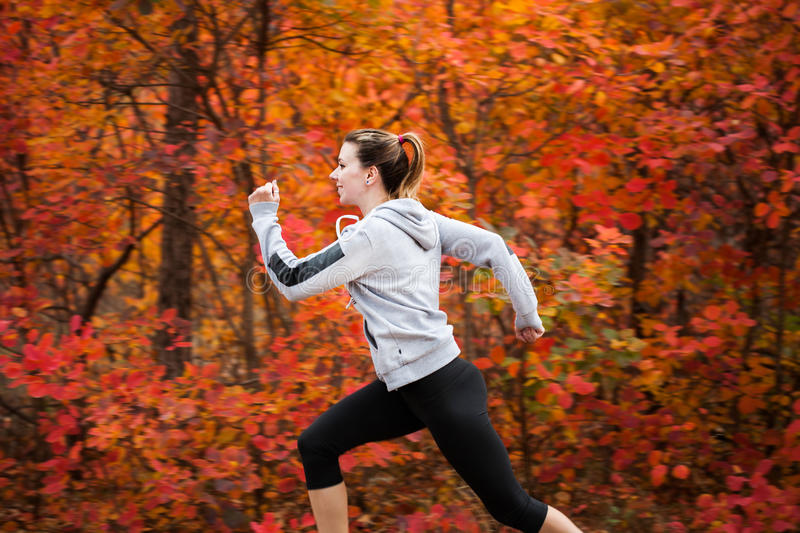 Attractive young woman running through autumn forest royalty free stock photography