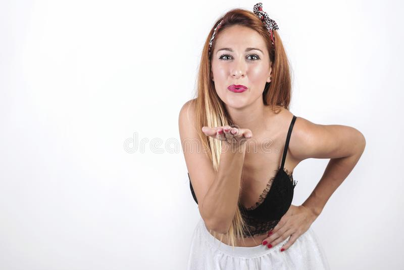 Attractive young woman sending a kiss. On White background royalty free stock photos