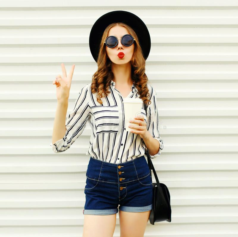 Attractive young woman sending sweet air kiss holding coffee cup in black round hat, shorts, white striped shirt on white wall stock photo