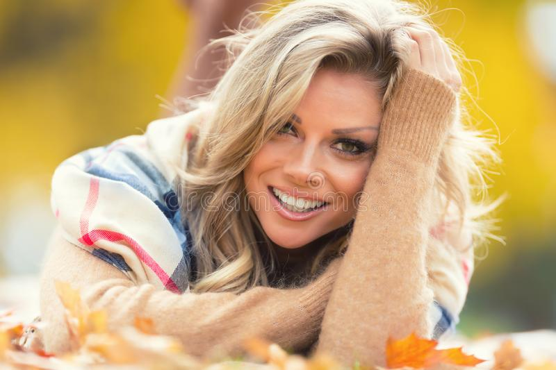 Attractive young woman with sensual smile lies in autumn park stock photos