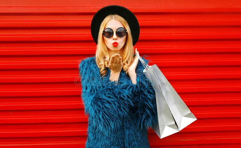Attractive young woman with shopping bags blowing red lips sending sweet air kiss, stylish female model wearing blue faux fur coat royalty free stock image