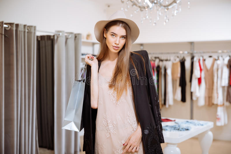 Attractive young woman with shopping bags in clothes shop stock image