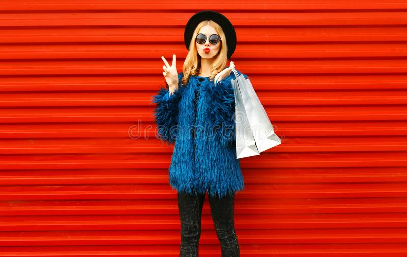 Attractive young woman with shopping bags, stylish female model showing peace gesture wearing blue faux fur coat, round hat stock photo