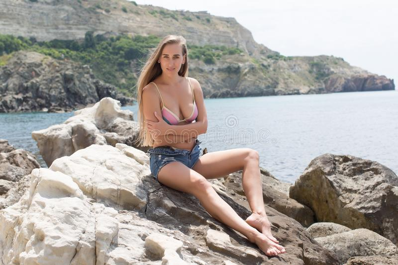 Attractive young woman sits on coastal boulder stock images