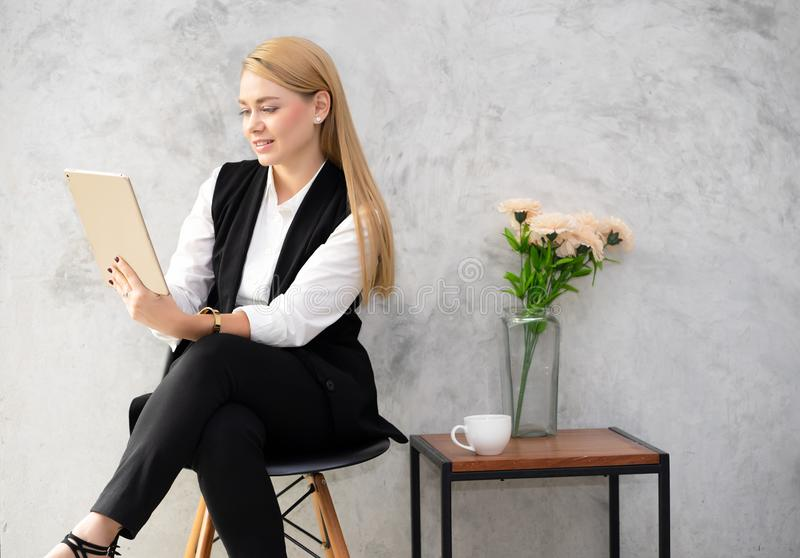 Attractive young woman sitting on chair working with a tablet on gray cement texture background.Loft style. stock photography