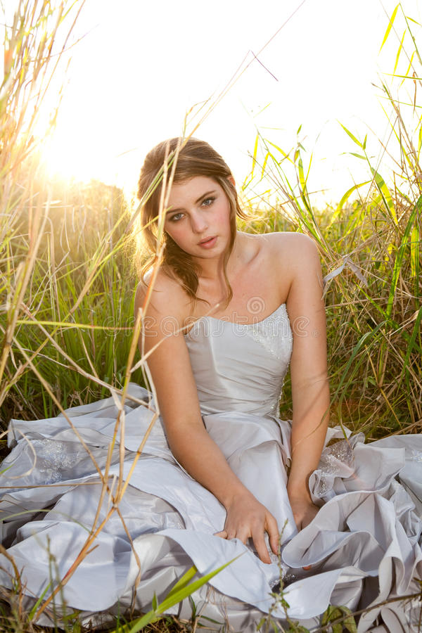 Attractive Young Woman Sitting in the Grass royalty free stock image