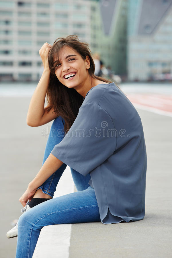 Attractive young woman sitting outdoors and laughing. Portrait of attractive young woman sitting outdoors and laughing royalty free stock image