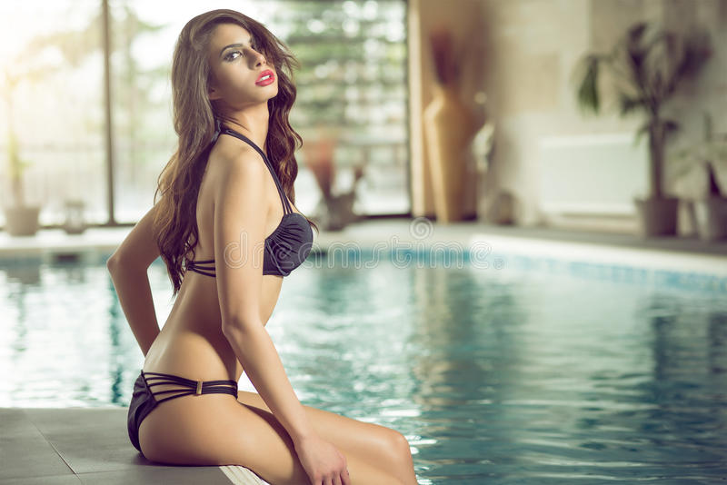 Attractive young woman sitting on pool edge royalty free stock photo