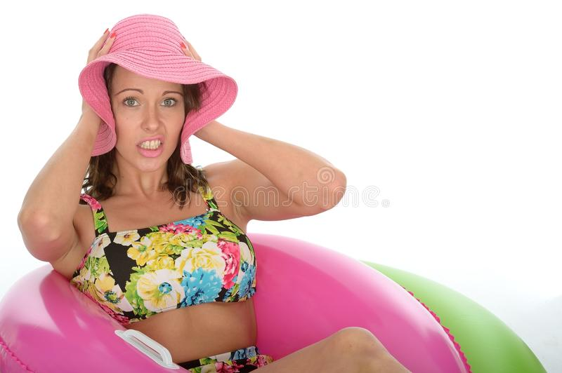 Attractive Young Woman Sitting in Rubber Ring Wearing a Swimsuit. A DSLR royalty free image, of attractive shocked unhappy young woman sitting in colourful royalty free stock images