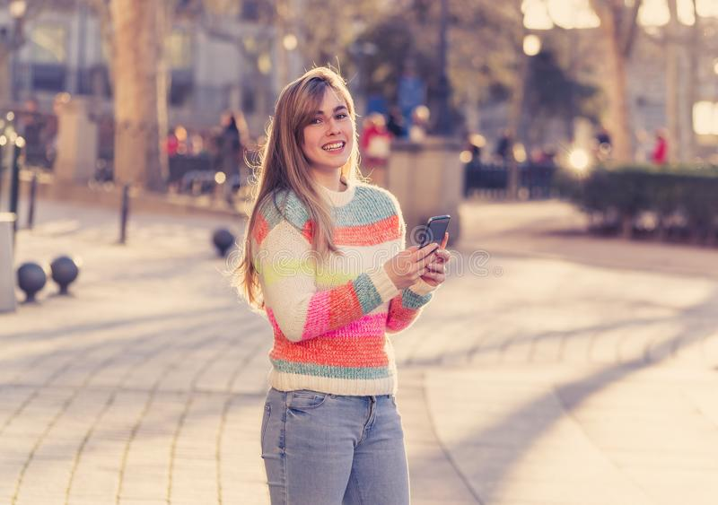 Attractive young woman on smart phone checking social media mobile apps outside city royalty free stock photo
