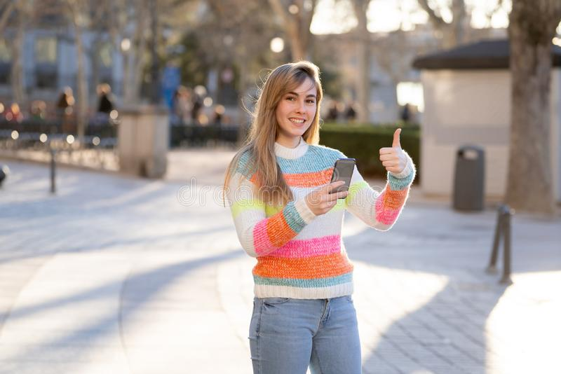 Attractive young woman on smart phone checking social media mobile apps outside city stock photo