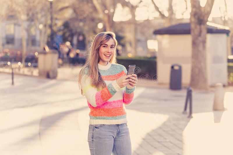 Attractive young woman on smart phone checking social media mobile apps outside city royalty free stock photography