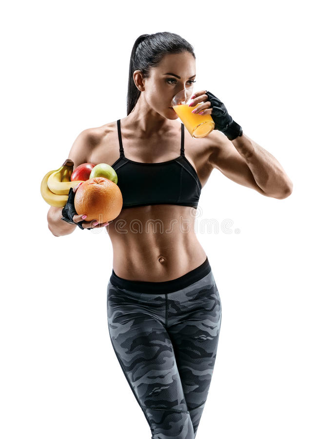 Attractive young woman in sports wear hold fresh fruits and drink orange juice. stock photo