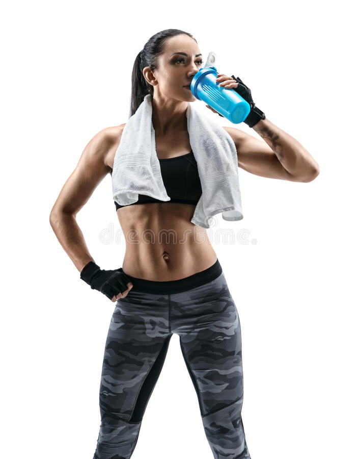 Attractive young woman in sports wear and with towel on shoulders drink protein cocktail in special shaker royalty free stock image