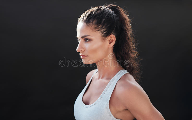 Attractive young woman in sportswear. Close up shot of attractive young woman in sportswear posing on black background. Healthy female model looking focused in stock images