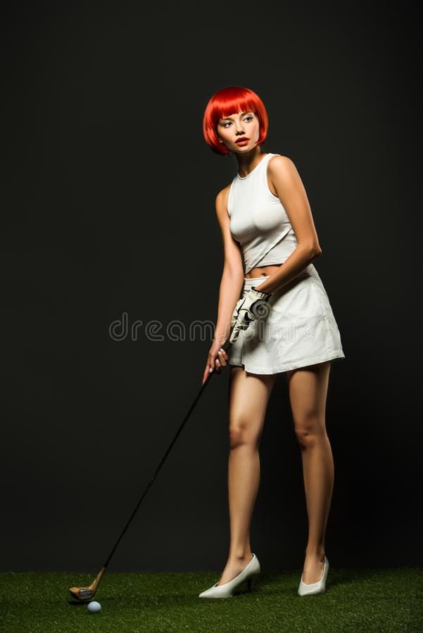 attractive young woman in sportswear and high heels playing golf on green grass royalty free stock photography