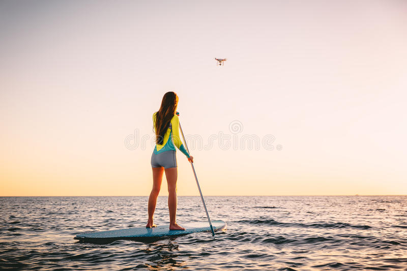 Attractive young woman Stand Up Paddle Surfing and drone copter with beautiful sunset colors royalty free stock image