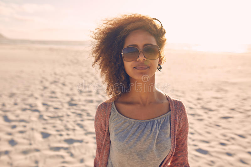 Attractive young woman standing on a beach stock photo