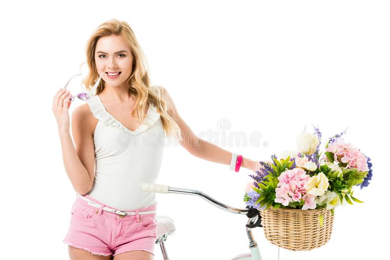 Attractive young woman standing by bicycle with flowers in basket stock images