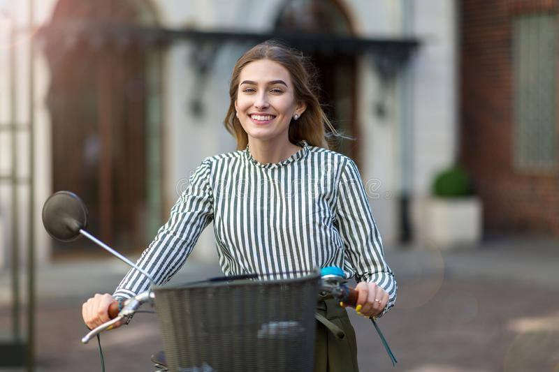 Young woman standing with her bicycle in the city royalty free stock image