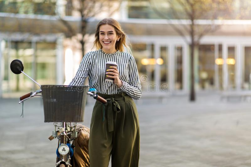 Young woman standing with her bicycle in the city. Attractive young woman standing with her bicycle in the city royalty free stock photo