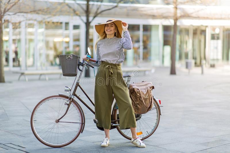 Young woman standing with her bicycle in the city stock photo