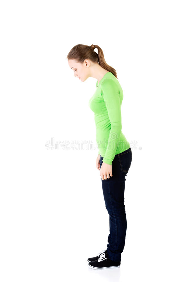 Attractive young woman standing and looking down. Side view. royalty free stock photos