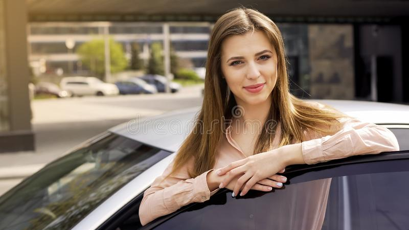Attractive young woman standing near auto and posing for camera, buying a car royalty free stock photography