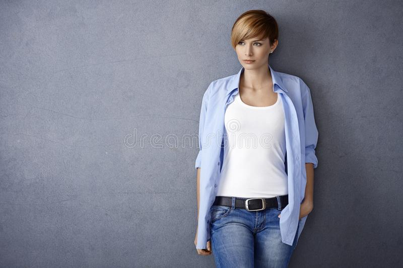 Attractive young woman standing by wall stock images