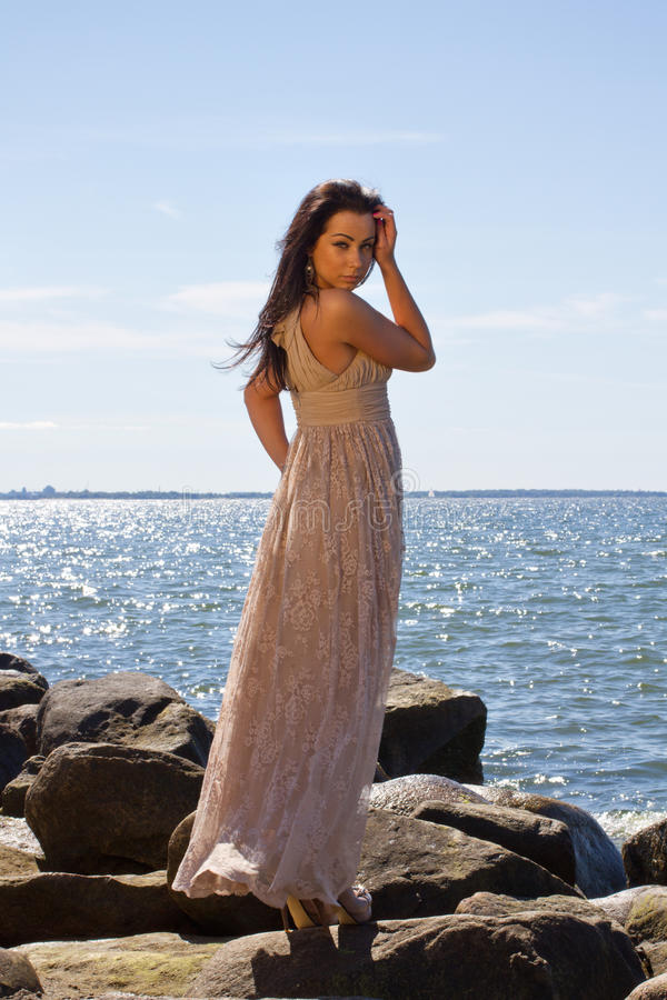 Attractive young woman on the stones stock images